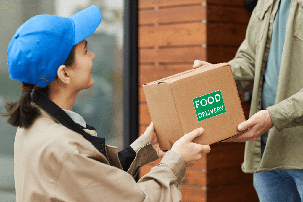 Young courier giving the cardboard box to man while they standing outdoors she delivering food